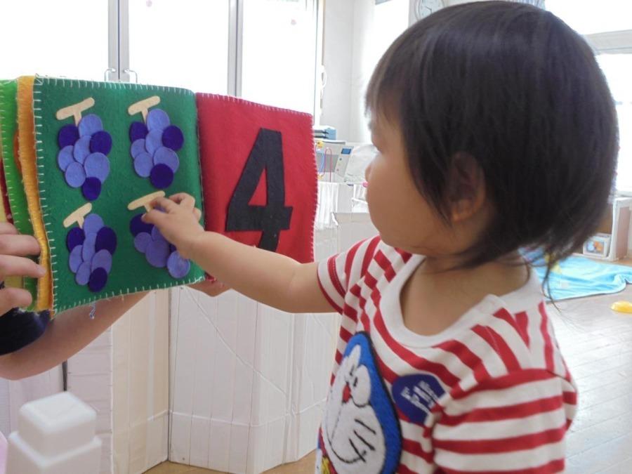 こども愛々保育園 南大泉(保育士の求人)の写真:毎日行う知育の時間。 手作りの布絵本で数字を 見ています。