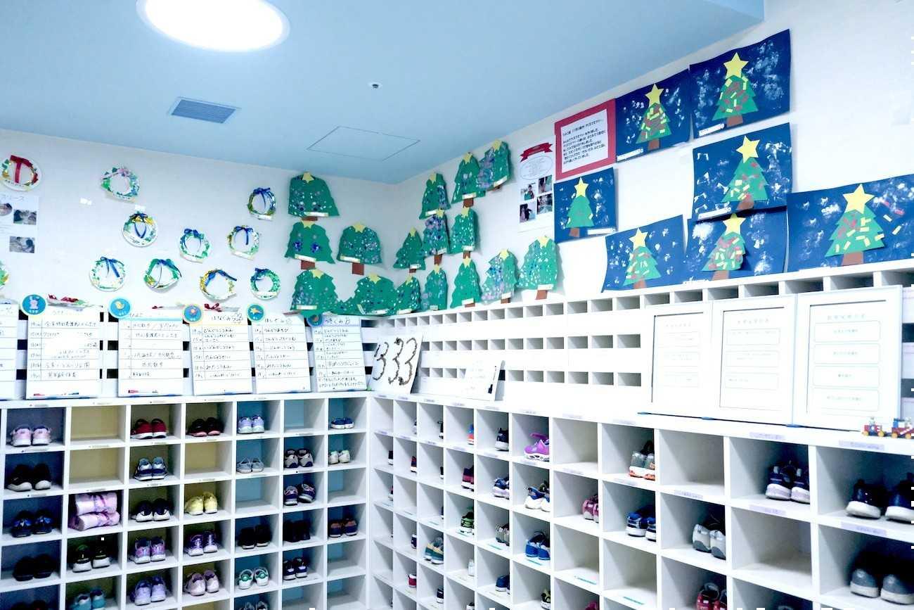 花房山目黒駅前保育園333の入り口の棚や壁に子どもたちの作品が飾ってある様子